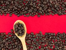 Coffee beans close-up on a red background and in a wooden spoon royalty free stock photos