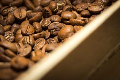 Coffee beans close up and wooden box.  royalty free stock image