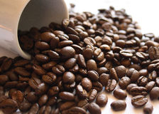 Coffee beans closeup. Pouring from espresso cup Stock Photo