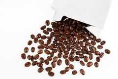 Coffee beans. Closeup of coffee beans spilling from packet on plain background Royalty Free Stock Image