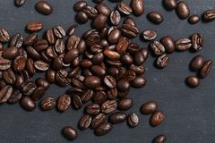 Coffee beans  on black board. Coffee beans in coconut shell bowl on black slate board background Royalty Free Stock Photography