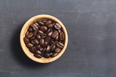 Coffee beans  on black board. Coffee beans in coconut shell bowl on black slate board background Royalty Free Stock Image