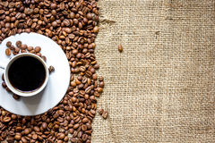 Coffee beans, coffe cup on linen cloth background top view Royalty Free Stock Photo