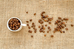 Coffee beans, coffe cup on linen cloth background top view Royalty Free Stock Photos