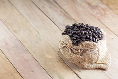 Coffee beans in coffee bag made from burlap on wooden surface Royalty Free Stock Image
