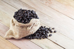 Coffee beans in coffee bag made from burlap on wooden surface Royalty Free Stock Photography