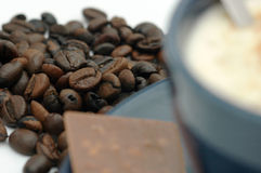 Coffee beans and coffee cup. Coffe beans behind a coffee cup. Foucus on beans royalty free stock photos