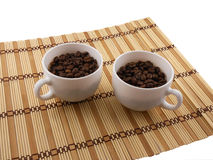 Coffee beans, coffee cup on bamboo background Stock Image