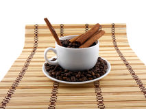 Coffee beans with coffee cup, cinnamon on bamboo background Stock Images