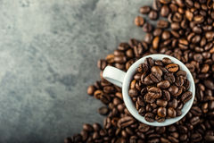 Coffee beans. Coffee cup full of coffee beans. Toned image.  Royalty Free Stock Photo