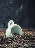 Coffee beans. Coffee cup full of coffee beans. Toned image.  Stock Photography
