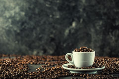 Coffee beans. Coffee cup full of coffee beans. Toned image.  Royalty Free Stock Photography