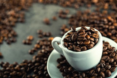 Coffee beans. Coffee cup full of coffee beans. Toned image.  Stock Images