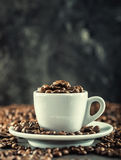 Coffee beans. Coffee cup full of coffee beans. Toned image.  Stock Image