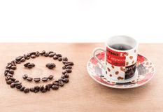 Coffee beans and coffee cup on the table. Coffee beans and coffee cup on the wood table Stock Photos