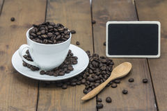 Coffee beans in a coffee cup. On a wooden floor Stock Photo