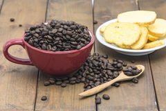 Coffee beans in a coffee cup. On a wooden floor Stock Photography