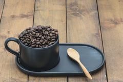 Coffee beans in a coffee cup. On a wooden floor Royalty Free Stock Images