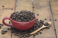 Coffee beans in a coffee cup. On a wooden floor Royalty Free Stock Image