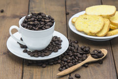 Coffee beans in a coffee cup on a wooden floor. Coffee beans in a coffee cup Stock Photos