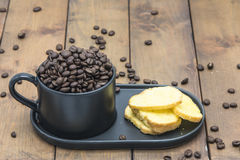 Coffee beans in a coffee cup. On a wooden floor Stock Image