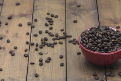 Coffee beans in a coffee cup. On a wooden floor Royalty Free Stock Photography