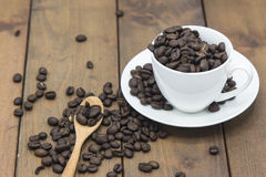 Coffee beans in a coffee cup. On a wooden floor Royalty Free Stock Photos