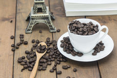 Coffee beans in a coffee cup. On a wooden floor Stock Photos