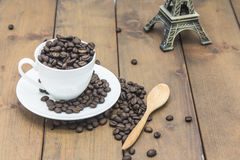 Coffee beans in a coffee cup. On a wooden floor Royalty Free Stock Photo