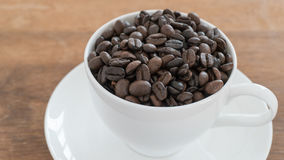 Coffee beans in coffee cup. On wooden table Royalty Free Stock Photography