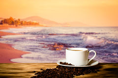 Coffee beans and coffee in cup on wooden table opposite a blurred background royalty free stock photo