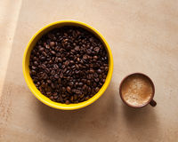 Coffee beans and coffee espresso. Yellow bowl with coffee beans and coffee espresso cup on table Royalty Free Stock Photo
