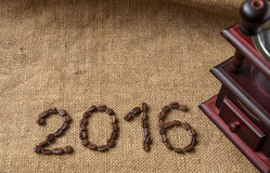 Coffee beans and coffee grinder, close up on the background of burlap sack, 2016 happy new year Royalty Free Stock Image