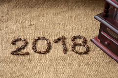 Coffee beans and coffee grinder, close up on the background of burlap sack, 2018 happy new year Stock Images