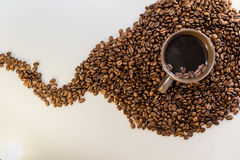 Coffee beans and coffee in a mug. Close up of coffee beans and a mug of coffee Royalty Free Stock Images