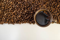Coffee beans and coffee in a mug with copy space. Close up of coffee beans and a mug of coffee royalty free stock photography