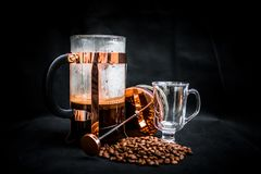 Coffee Beans Beside Coffee Press and Glass Cup Stock Photo