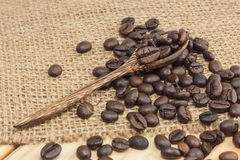 Coffee beans on a coffee spoon. Coffee beans on sackcloth and wood background, selective focus Stock Image
