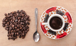 Coffee beans and coffee. Coffee, spoon and coffee beans on the wood table Royalty Free Stock Photo
