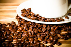 Coffee beans and coffee in white cup on wooden table for backgro Stock Photography