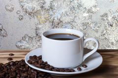 Coffee beans and coffee in white cup on the wooden table opposit Stock Image