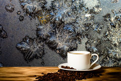 Coffee beans and coffee in white cup on the wooden table opposit Stock Images