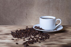 Coffee beans and coffee in white cup on wooden table opposite a Stock Photography