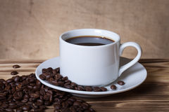 Coffee beans and coffee in white cup on wooden table opposite a Stock Photo