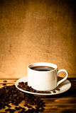 Coffee beans and coffee in white cup on wooden table opposite a Stock Images