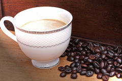 Coffee beans with coffee. Royalty Free Stock Images