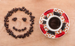 Coffee beans and coffee. On wood table Royalty Free Stock Photos