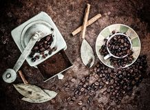 Coffee beans coming out of cup with grinder background. Overhead view of coffee beans pouring out of a cup and old grinder to grind coffee and decorating some Royalty Free Stock Photos