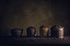 Coffee beans in container on wood floor and old paper vintage ag. Ed background or texture royalty free stock image