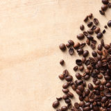 Coffee beans with copy space. Scattered coffee beans on textured brown table. Top view, copy space Royalty Free Stock Photo